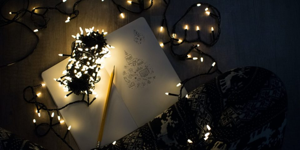 A notebook surrounded by Christmas lights on the floor in front of a person's legs