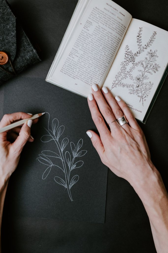 A woman drawing with a white pencil on black paper