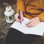 Person in yellow sweater drawing in a notebook