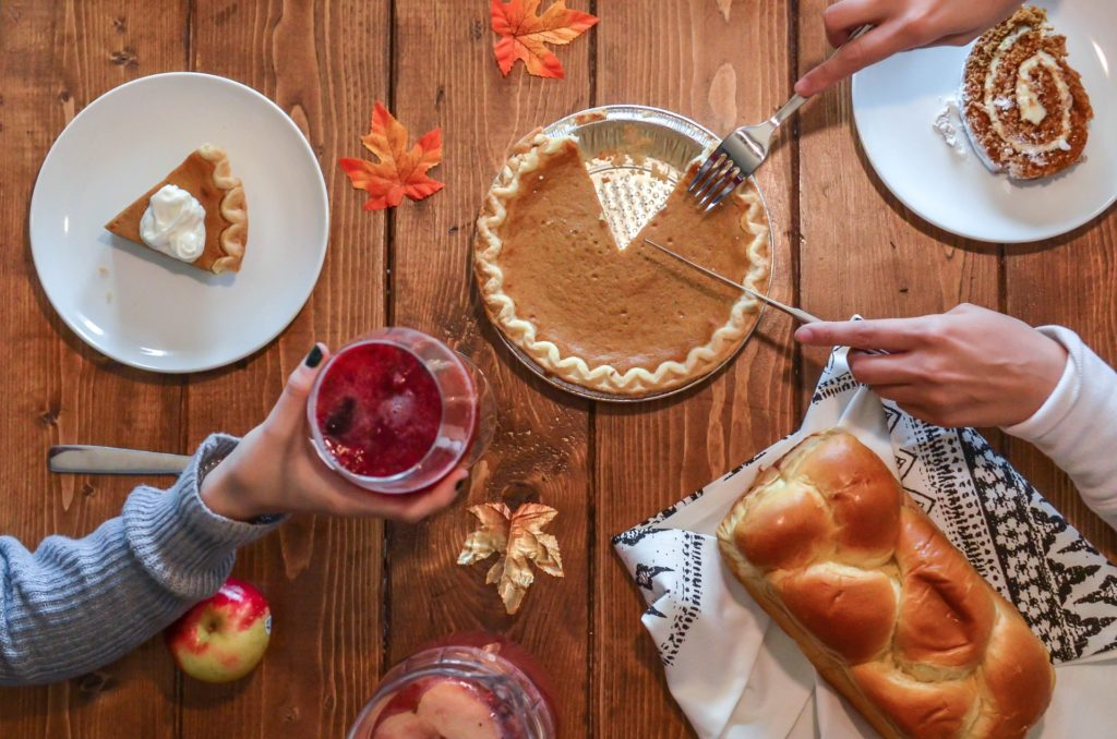 Photo of a table with people enjoying Thanksgiving desserts