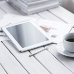 A tablet and stylus on a table next to a coffee cup