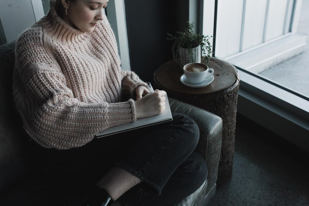 Woman in a sweater practicing how to journal effectively