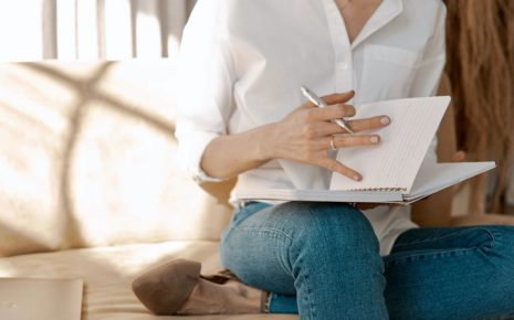 A woman in white who is practicing effective journaling